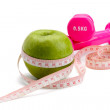 An apple, a measuring tape and dunbbell — Stock Photo #33872775