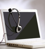 Hoofdtelefoon met laptop op Bureau — Stockfoto