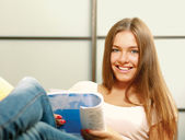 Woman on the couch with a book — Stock Photo