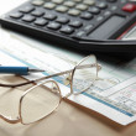 Pen and calculator on stocks — Stock Photo
