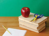 Red apple and scissors on pile of books — Stockfoto