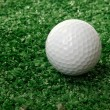 Golf ball ower green grass — Stock Photo