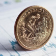 A golden coin on diagram papers — Stock Photo #34823857