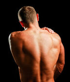 Muscular man with back neck ache — Stock Photo
