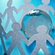 Paper people standing in a circle around glass globe — Stock Photo