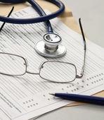Penna, stetoskop, mapp med papper och glas — Stockfoto