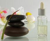 Flaskor eterisk olja och uppsättning av stenar med blomma — Stockfoto