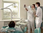 Молодая женщина с стоматологом в стоматологической хирургии — Стоковое фото