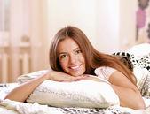 Beautiful woman ying on bed — Stock Photo