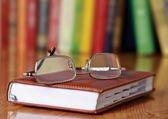 Book with glasses on the desk against books — Stock fotografie