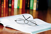 Book with glasses on the desk — Stok fotoğraf