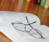 Book with glasses on the desk against books — Stok fotoğraf
