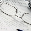 Financial charts, a pen and glasses — Stock Photo