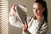Young woman doctor is standing near window — Stockfoto