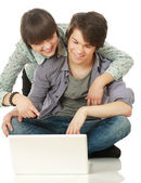 Couple sitting on the floor behind a laptop — Stock Photo