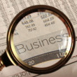 Looking through magnifying glass to financial report — Stockfoto