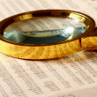 Looking through magnifying glass to financial report — Zdjęcie stockowe