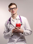 Doctor with stethoscope holding heart — Stock Photo