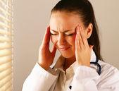 Kvinnliga läkare med huvudet smärta — Stockfoto