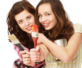 Young girls with brushes and paintings — Stock Photo
