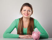 Beautiful woman with piggy bank — Stock Photo