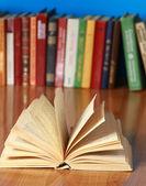 Libro sulla scrivania contro libri — Foto Stock