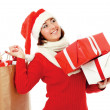Smiling girl in santa hat with bag full of xmas gift isolated on white background. — Stock Photo