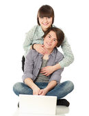 A couple sitting on the floor behind a laptop — Stock Photo