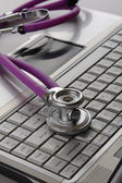 A violet stethoscope on a white laptop computer — Stockfoto