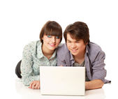 Couple lying on the floor behind a laptop — Stock Photo