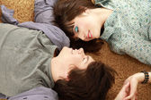 A young couple lying on the floor — Stock Photo