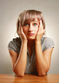 A young frightened woman sitting at the desk — Stock Photo