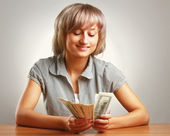 A young woman holding dollars — Stock Photo