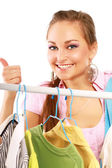 Happy girl in clothing store showing thumbs up — Stock Photo