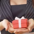 Female hands holding a gift — Stockfoto