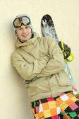Um snowboarder em pé contra a parede — Fotografia Stock