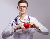 Male doctor with stethoscope holding heart — Stock Photo
