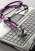 A violet stethoscope on a white laptop computer — Stock Photo