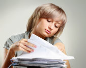 A tired young woman sitting at the desk — Stock Photo