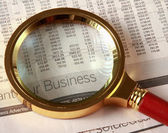 Looking through magnifying glass to financial report — Stock Photo