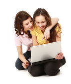 Two girls twins with laptop isolated on the white — Stock Photo