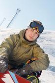 Snowboarder sitzend auf einer skipiste — Stockfoto