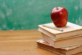 Bir kalem ve bir yığın kitap üzerinde kırmızı elma — Stok fotoğraf