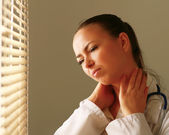 Female doctor with head pain — Stock Photo