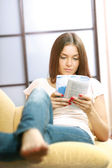 Woman on the couch with a book — Stockfoto
