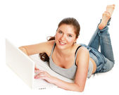 Young woman lying on bed with laptop — Stock Photo