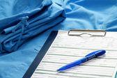 Portapapeles y una pluma en un uniforme médico — Foto de Stock