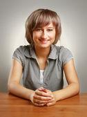Una joven universitaria sentado en el escritorio — Foto de Stock