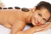 Smiling woman receiving a therapy with hot stones in spa center — Stock Photo