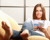 Beautiful young woman on the couch with a book. — Stock Photo